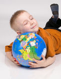 The boy and globe. The boy sleeps on the globe on a grey background Stock Image