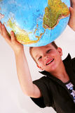 Boy with globe. Boy is holding the world in his hands Royalty Free Stock Image