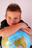 Boy with globe. Boy is holding the world in his hands Stock Image