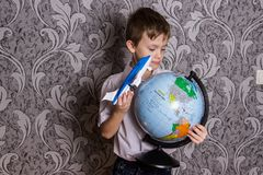 The boy stands with a globe and an airplane in his hands royalty free stock photo