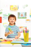 Boy with glue stick and pencils Royalty Free Stock Photo