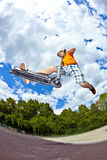 Boy goes airborne with his scooter Stock Photography