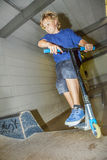 Boy goes airborne with his scooter Royalty Free Stock Photography