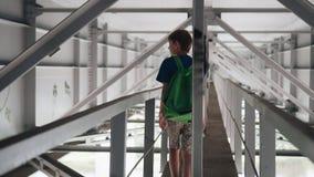 The boy goes along a long metal corridor under the bridge. Nice atmospheric footage stock video footage