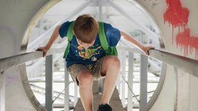 The boy goes along the metal corridor under the bridge. He climbs through the hatch. Cool footage in motion. Wonderful emotional shots stock video