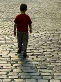 Boy goes away. On an empty street Royalty Free Stock Images