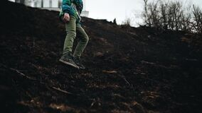 The boy goes down the slope with burnt grass. Beautiful dynamic frames