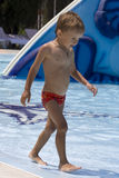 Boy goes on the edge of pool Royalty Free Stock Photo