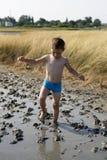 Boy goes on healing mud Stock Photos