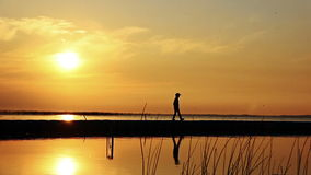 Boy goes on the pier along the river at sunset, REFLECTION IN WATER Teenagers stock video footage