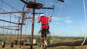 Boy goes on swinging beams stock video footage