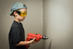 Boy in goggles with electric drill Royalty Free Stock Photos