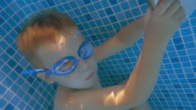 Boy in Goggles Holding Breath in Swimming Pool. Slow motion shot of little boy under water in swimming pool, he is holding his breath stock video