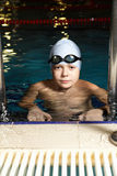 Boy in goggles at pool edge Stock Images