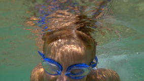 Boy in Goggles Swimming Under the Sea Water. Slow motion shot of little boy in goggles swimming under water in the sea towards the camera stock footage