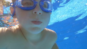 Boy in Goggles Under Water. Slow motion shot of little boy in goggles swimming under water in swimming pool stock video