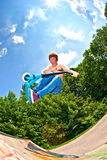 boy going airborne with a scooter Royalty Free Stock Photography
