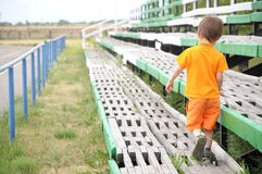 Boy going through the empty benches in the stadium Royalty Free Stock Photo
