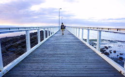 Boy going fishing on jetty. Boy walking on jetty with fishing rod at sunrise Stock Photography