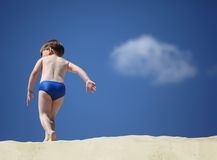 Boy going on sand,  rear view Stock Photos