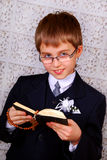 Boy going to the first holy communion. Portrait of the boy going to the first holy communion  with prayer book and rosary Stock Photography