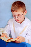 Boy going to the first holy communion with prayer. Young boy in white alb going to the first holy communion and praying with prayer book Royalty Free Stock Photos