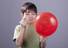 Boy going to pop balloon. A young boy with a smirk on his face gets ready to pop a ballooon royalty free stock photography