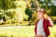 Boy going to throw apple in park Stock Images