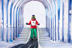Boy going up under safety archway using ski lift Stock Photos