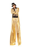 Boy in gold on stilts Stock Images
