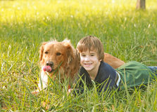 Boy and Golden Retriever. Little Boy Laying in Tall Grass with Golden Retriever royalty free stock images