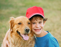 Boy and Golden Retriever. Boy Smiling Big and Hugging Golden Retriever stock photography