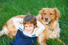 Boy and Golden Retriever. Boy Smiling Big Laying on Golden Retriever stock image