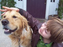Boy and golden retriever on porch. Young boy petting his pet golden retriever on porch of old house royalty free stock image