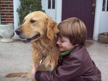 Boy and golden retriever portrait. Young boy hugging his pet golden retriever on porch of old brick house stock photo