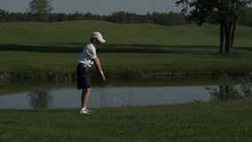 Junior golfer playing golf on summer with hitting shot on green grass stock video