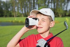 Boy golfer watching into rangefinder Royalty Free Stock Photography