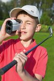 Boy golfer watching into rangefinder Stock Photography