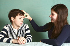 Boy got flip at forehead from sister. Preteen boy got flip at forehead from sister because of lost bet royalty free stock photo