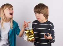 Boy got a simple mobile phone in a gift box, his sister laughing. On him Royalty Free Stock Photos
