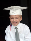Boy in Graduation Cap. Boy graduating from preschool, wearing white graduation cap. Black background Stock Photography