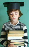 Boy in graduation cap with book pile Royalty Free Stock Photos