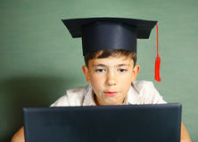 Boy in graduation cap with notebook Royalty Free Stock Photo