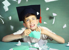 Boy in graduation cap  tear his copycook Stock Photography