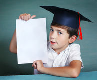 Boy in graduation cap whith white paper sheet Royalty Free Stock Photos