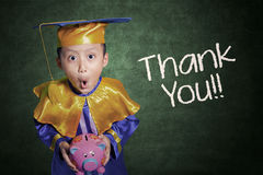 Boy with graduation gown holding piggybank Stock Images