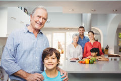 Boy with grandfather while family by kitchen table in background Stock Photos