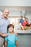 Boy with grandfather while family preparing food in background Stock Photography