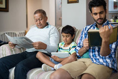 Boy with grandfather and father sitting on sofa. In living room at home Royalty Free Stock Photo