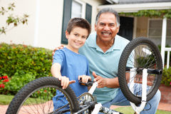 Boy and grandfather fixing bike Royalty Free Stock Photo